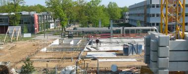 Photographie couleur - format panoramique- du chantier de construction, présentant les fondations
