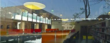 Photo l'intérieur de la BU lettres prise depuis l'extérieur avec reflet du ciel et des arbres