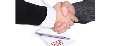 """Photographie d'une poignée de main entre deux hommes, un bloc de prise de note, un stylo et l'inscription """" valid"""" en rouge en arrière plan."""