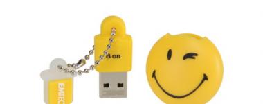 Photographie sur fond blanc d'une clé USB jaune avec son capuchon rond décoré d'un motif émoticone 'smile clin d'oeil'