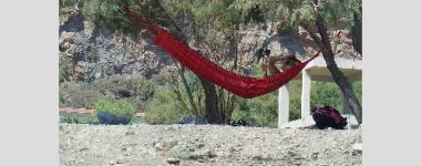 Photographie d'une femme lisant dans un hamac. Paysage méditerranéen au 1er et à l'arrière plan