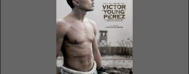 Affiche du film sur fond gris taupe présentant le boxeur torse nu, pantalon rayé de prisonnier, la cloture du camp en arrière plan