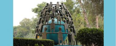 Photographie d'une sculpture dans un parc composée d'une boule bleue au centre, entourée de silhouettes humaines en métal brun, empilées comme pour un chateau de cartes. La boule et la structure circulaire des silhouettes reposent sur un socle bleu, ou est inscrit le mot FUTURO en lettres blanches.