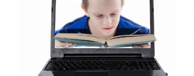 Photographie, d'un ordinateur portable ouvert. Sur l'écran s'affiche la photo d'un jeune garçon vêtu d'un pull bleu, lisant un livre, le livre sort du cadre de l'écran.
