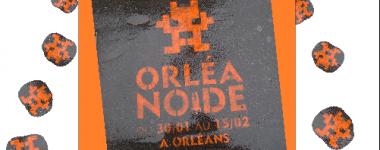 Photographie d'une peinture au pochoir orange sur un trottoir mouillé, sur un fond orange